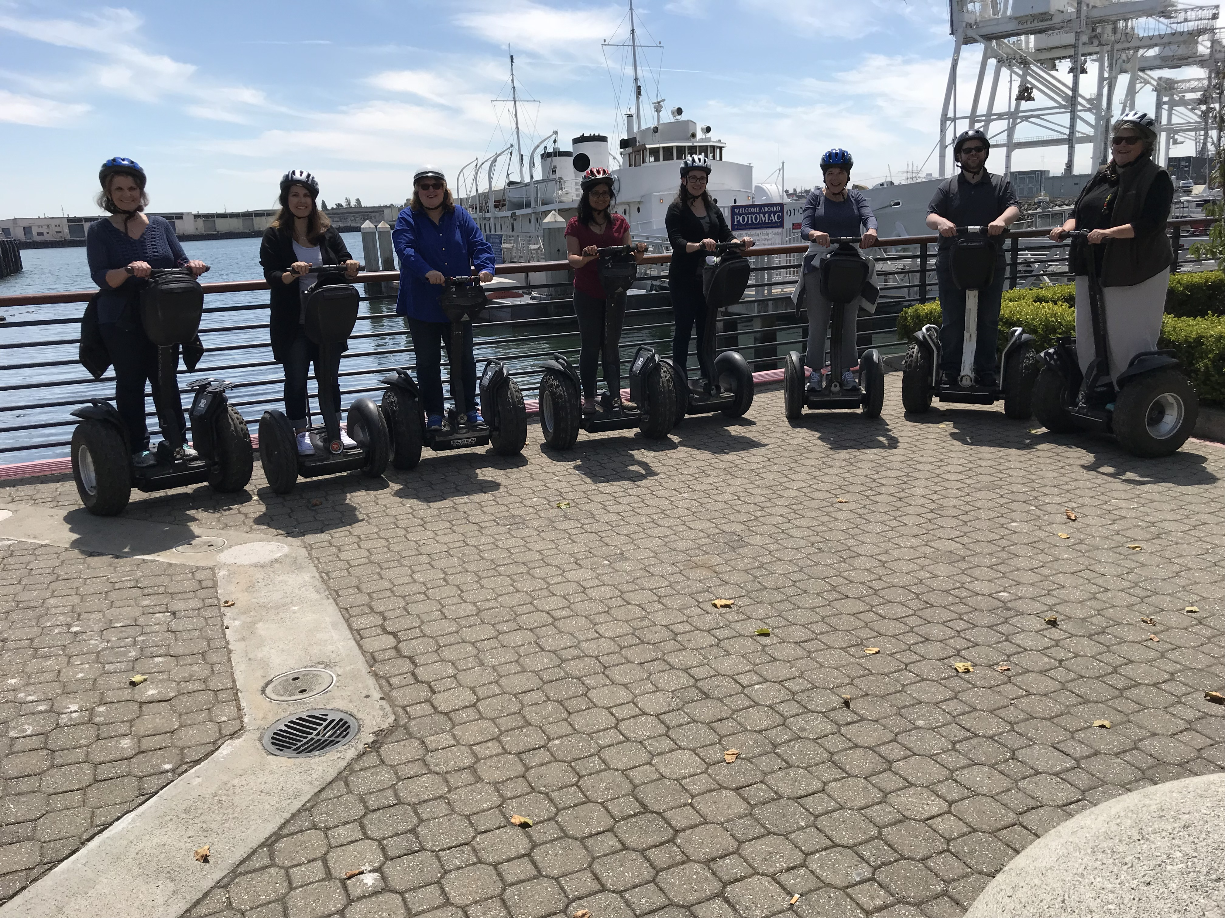 Row of people standing on segways near water and boats