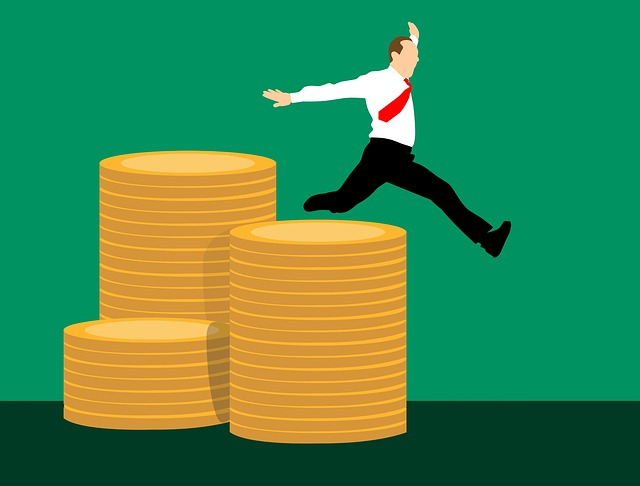 Business man jumping over stacks of giant coins