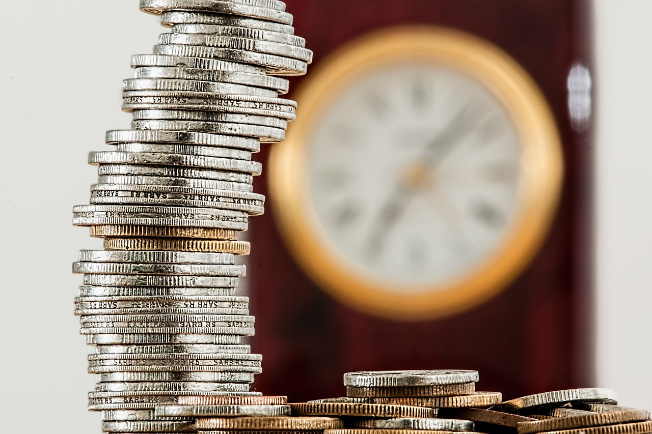 Coins stacked and piled high with clock in background